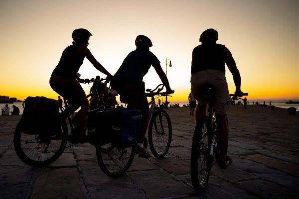 3 persone bici tramonto