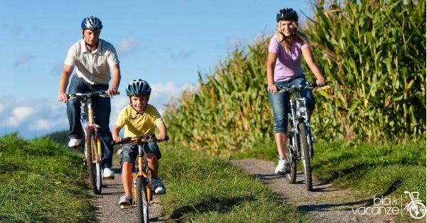 famiglia in bicicletta controluce